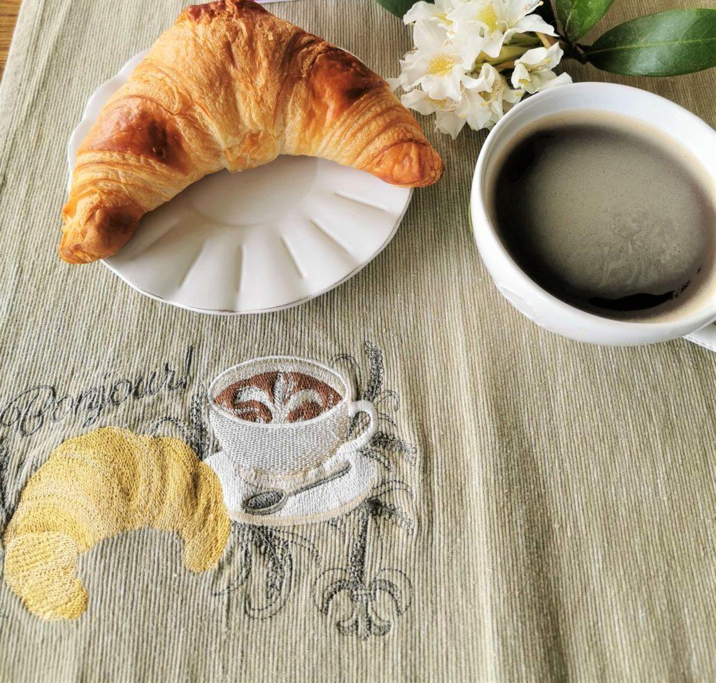 Leinenstischset mit Croissant und Café französischer Flair auf dem Tisch gegen Sehnsucht zuhause