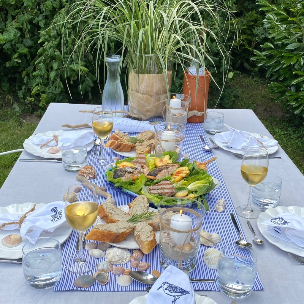 Maritime Tischdeko graue Leinentischdecke, gestreifter Tischläufer, Muscheln, Gräser und Fische für Meer Flair