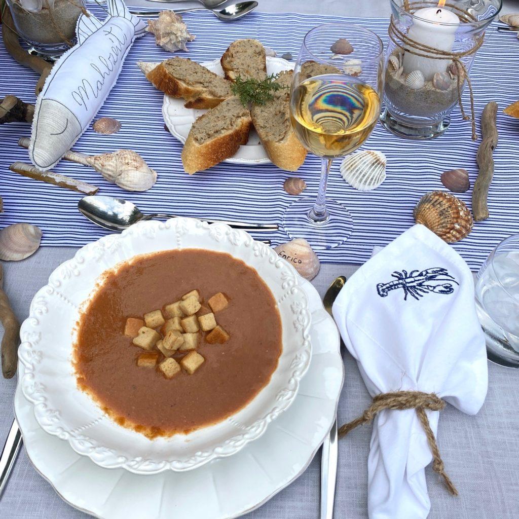Fischsuppe mit Crourons und maritimer Deko Streifen Muscheln und Wein